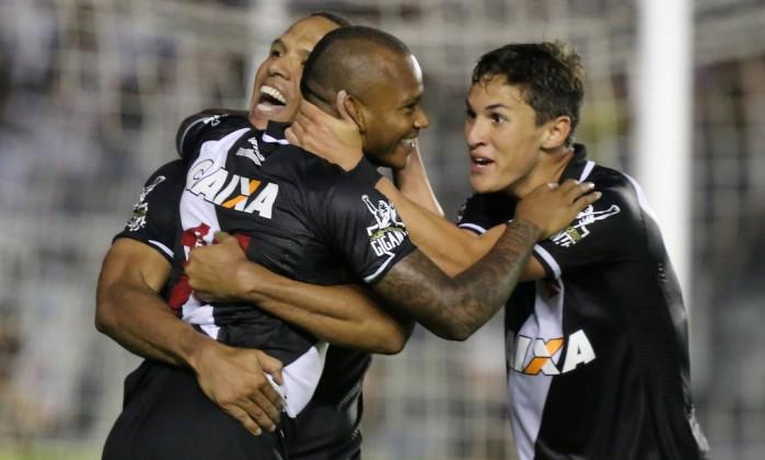 Manga Escobar é abraçado por Luis Fabiano (encoberto) e Mateus Vital ao marcar o segundo gol do Vasco Foto: Guilherme Pinto / Agência O Globo