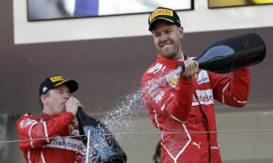 O alemão Sebastian Vettel e o finlandês Kimi Raikkonen celebram a dobradinha da Ferrari nas ruas do principado de Mônaco Foto: Claude Paris / AP