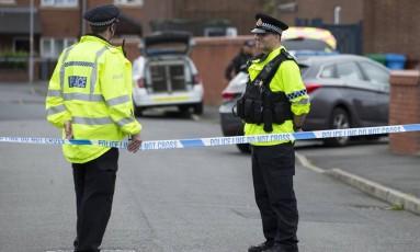 Policiais vigiam a entrada de uma rua durante uma operação em Manchester Foto: JOHN SUPER / AFP