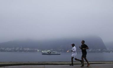 Nevoeiro visto da Enseada de Botafogo. Na foto, homens correm na orla Foto: Gabriel de Paiva / Agência O Globo