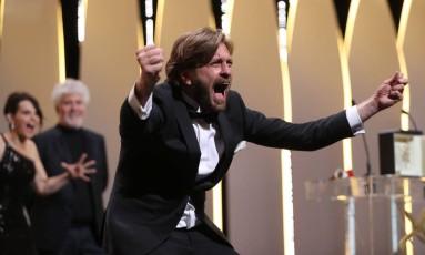 O diretor sueco Ruben Östlund pede para a plateia rugir junto com ele após vencer a Palma de Ouro do 70º Festival de Cannes, encerrado na noite deste domingo Foto: VALERY HACHE / AFP