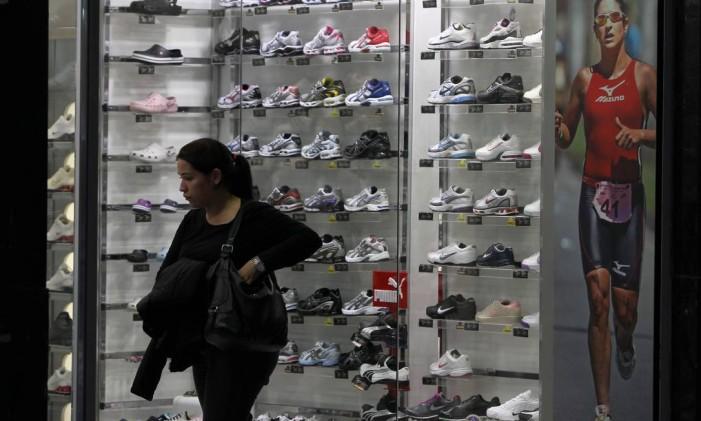Consumidora analisa preços de tênis em loja no centro de São Paulo antes de comprar Foto: Michel Filho / Agência O Globo