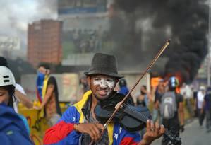 O violinista Wuilly Arteaga toca seu novo instrumento durante um protesto contra o presidente venezuelano, Nicolás Maduro Foto: LUIS ROBAYO / AFP