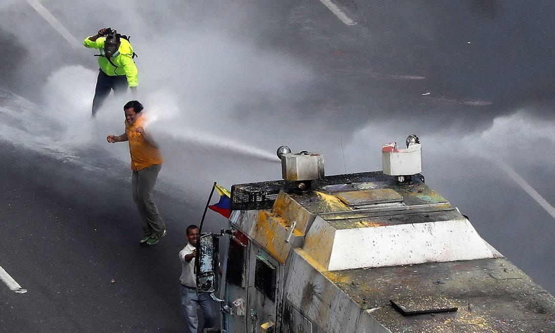 O deputado da oposição, Carlos Paparoni, é atingido por um jato de água durante marcha de políticos Foto: CARLOS GARCIA RAWLINS / REUTERS