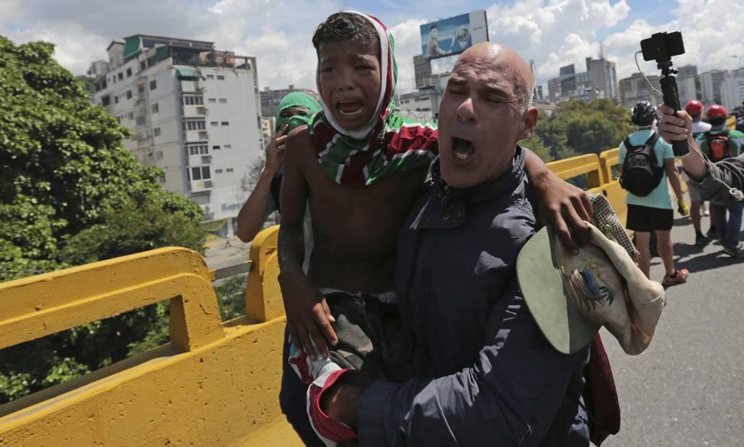 Homem retira um menino da área dos confrontos entre manifestantes e policiais Foto: Fernando Llano / AP