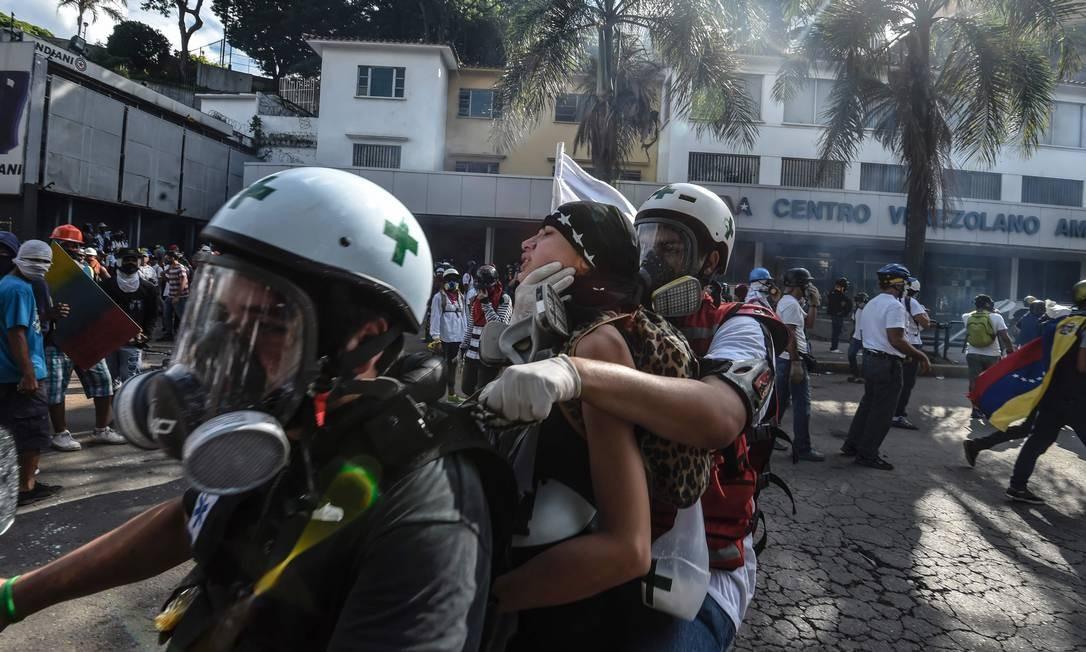 Paramédicos usam motos para socorrer feridos nos confrontos Foto: JUAN BARRETO / AFP