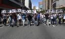 """Ativistas opositores carregam placas dizendo """"com violência perdemos tudo"""" em protesto contra o presidente venezuelano, Nicolás Maduro, em Caracas Foto: JUAN BARRETO / AFP"""