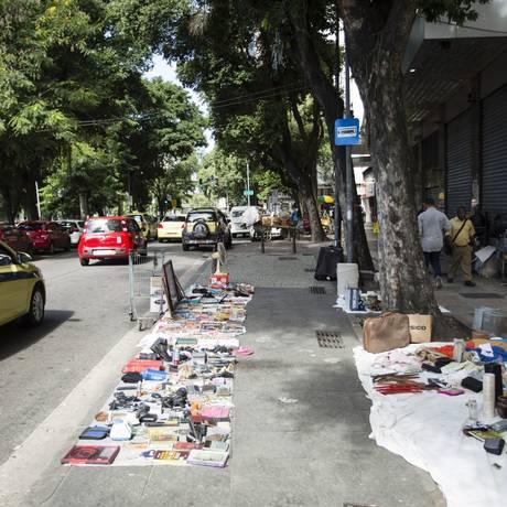 Mercadorias ficam espalhadas em cima de panos na calçada Foto: Fernando Lemos / Agência O Globo