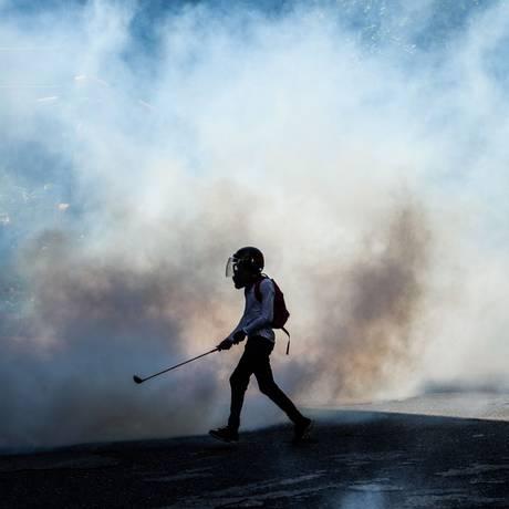 Manifestante da oposição caminha por nuvem de fumaça em protesto contra governo em Caracas Foto: FEDERICO PARRA / AFP