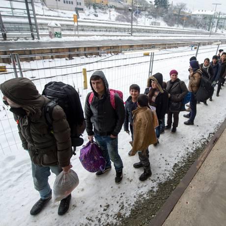 Refugiados caminham em fila em uma estação de trem em Passau, na Alemanha Foto: Armin Weigel / AP