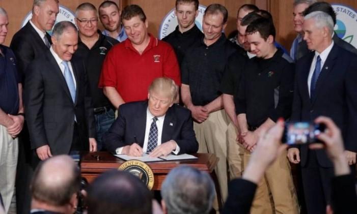 Trump assina a ordem executiva ao lado de Scott Pruitt, diretor da EPA (terceiro à esquerda) e o vice-presidente Mike Pence (à direita) Foto: Pablo Martinez Monsivais / AP