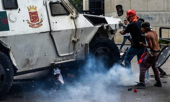 Jovem preso embaixo de veículo blindado das forças de segurança venezuelana durante um protesto contra o presidente Nicolás Maduro Foto: FEDERICO PARRA / AFP