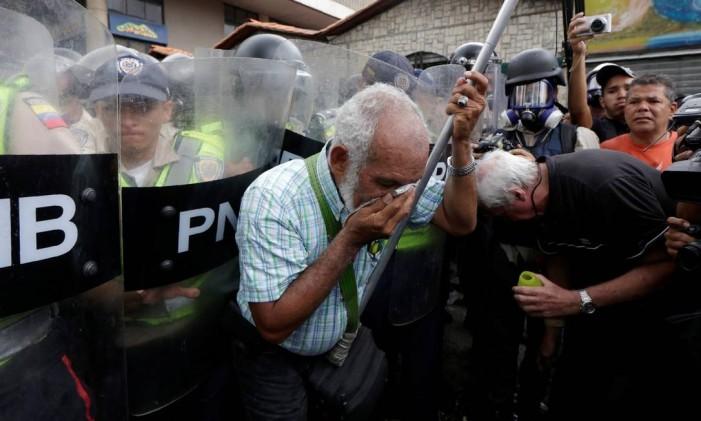 Um idoso cobre o rosto sofrendo os efeitos do gás de pimenta jogado pelas forças de segurança durante protesto contra o presidente venezuelano, Nicolás Maduro Foto: MARCO BELLO / REUTERS