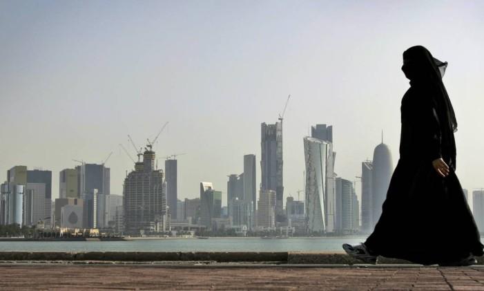 Uma mulher caminha em frente à cidade de Doha, capital do Qatar Foto: Kamran Jebreili / AP