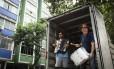 Depois de tempos difíceis em que era faz-tudo do prédio e dormia ao lado da lixeira, Paulo Garcia de Souza (de zabumba na mão) ensaia no baú de seu caminhão, em frente ao apartamento que comprou em Laranjeiras Foto: Fernando Lemos / Agência O Globo