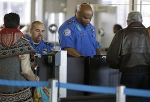 Agentes de segurança conferem a documentação de passageiros no Aeroporto Internacional O'Hare, em Chicago Foto: Nam Y. Huh / AP