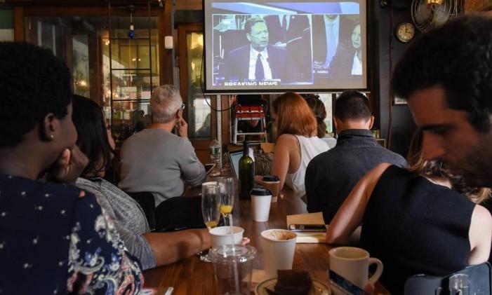 Pessoas assistem o testemunho do ex-diretor do FBI James Comey em um restaurante no Brooklyn, em Nova York. Americanos em todo o país lotaram bares e restaurantes para ver o testemunho de Comey sobre suas conversas com o presidente Donald Trump Foto: STEPHANIE KEITH / AFP