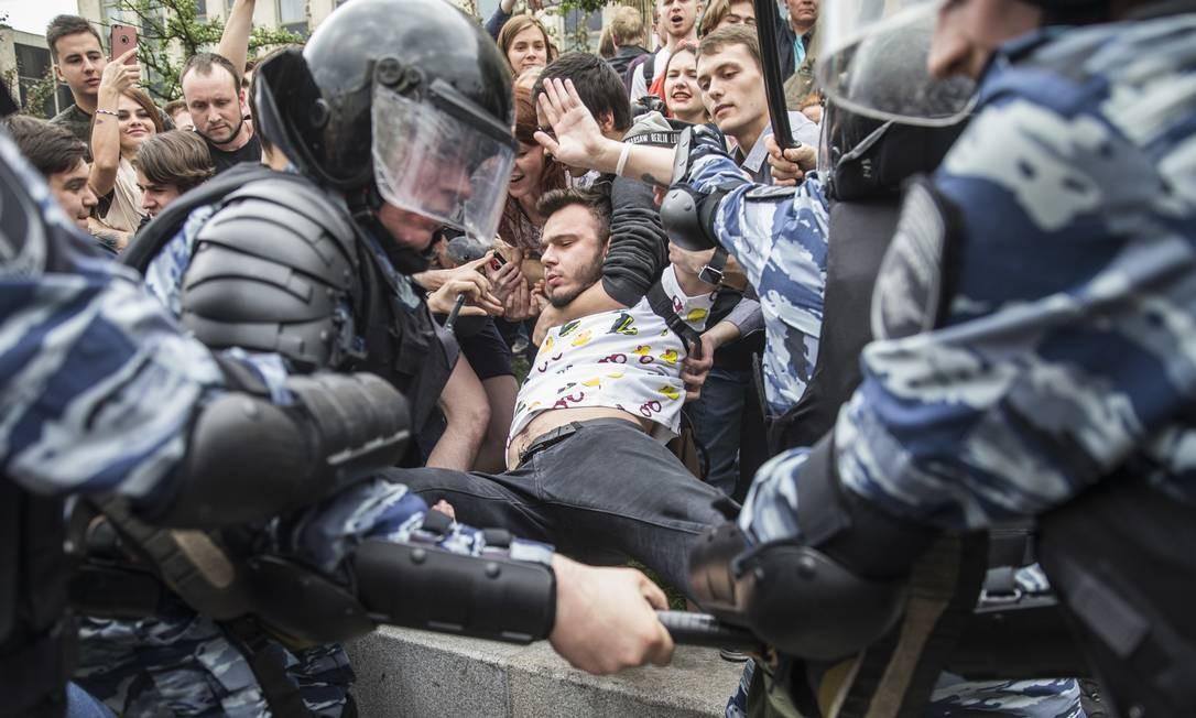 Polícia detém um manifestante em Moscou. Multidão foi às ruas mostrar indignação com a corrupção entre as autoridades do país e pedem alternância no poder Foto: Evgeny Feldman / AP