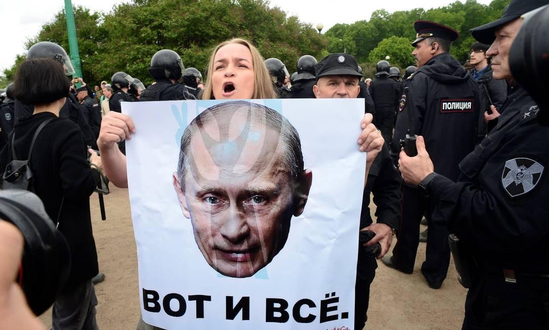 Uma mulher segura um pôster com a foto do presidente russo, Vladimir Putin, durante um protesto no centro de São Petersburgo Foto: OLGA MALTSEVA / AFP