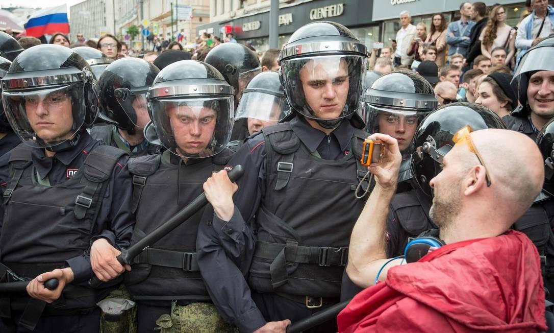 Manifestante tira fotos da política durante protesto no centro de Moscou. Milhares de russos foram às ruas em dezenas de cidades, incluindo perto do Kremlin em Moscou, onde a tropa de choque tentava dispersar a multidão Foto: MLADEN ANTONOV / AFP