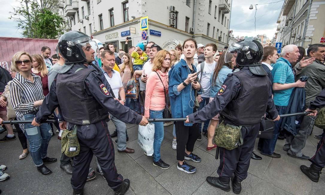 Policiais bloqueiam passagem de manifestantes durante protesto no centro de Moscou. Esta segunda-feira é feriado na Rússia, dia em que o país comemora a sua independência em 1990 antes da queda da União Soviética Foto: MLADEN ANTONOV / AFP