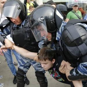 Jovem que protestava é detido pela polícia durante uma manifestação no centro de Moscou, na Rússia. As forças de segurança russas prenderam quase mil pessoas em protestos contra o presidente Vladimir Putin Foto: Alexander Zemlianichenko / AP