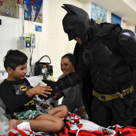 O Batman argentino com o menino Pablo Valdez, de sete anos, internado com uma infecção que lhe impede de andar Foto: EITAN ABRAMOVICH / AFP