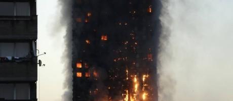 Fumaça e chamas são vistas no prédio na periferia de Londres Foto: Matt Dunham / AP
