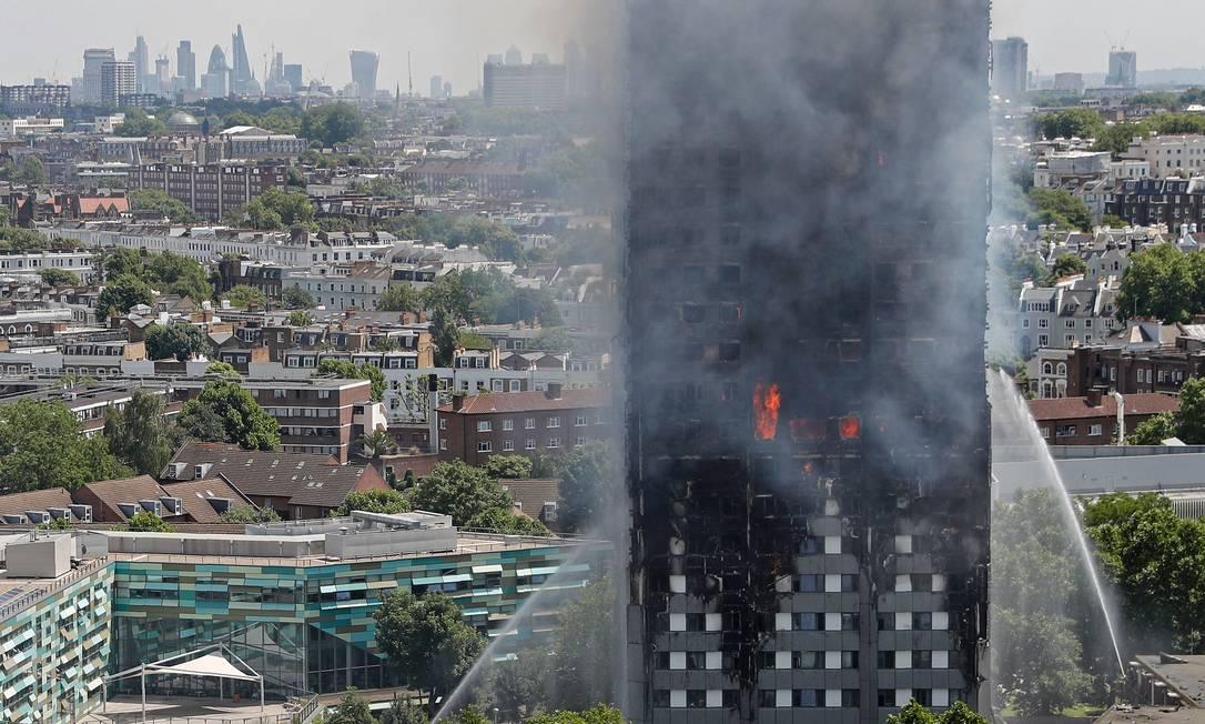 Fumaça e chamas são vistas no arranha-céu Grenfell Tower enquanto bombeiros tentam controlar o fogo em um bloco residencial, no oeste de Londres. Ao menos seis pessoas morreram quando o incêndio atingiu os apartamentos no meio da noite ADRIAN DENNIS / AFP