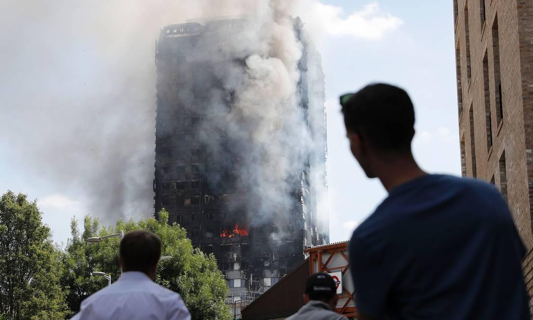 Pedestres observam a Grenfell Tower em chamas. Prédio passou por reforma em 2016 ADRIAN DENNIS / AFP