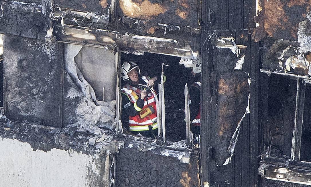 Bombeiro entre os destroços da Grenfell Tower queimada. Moradores criticam segurança falha no prédio: alarmes não soaram Rick Findler / AP