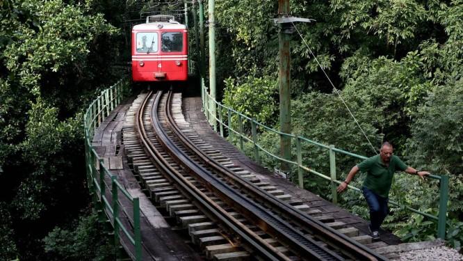 Um dos trens se aproxima de uma velha ponte de madeira: pedestre percorre o caminho ignorando o risco de ser surpreendido pela composição Foto: Custódio Coimbra / Agência O Globo