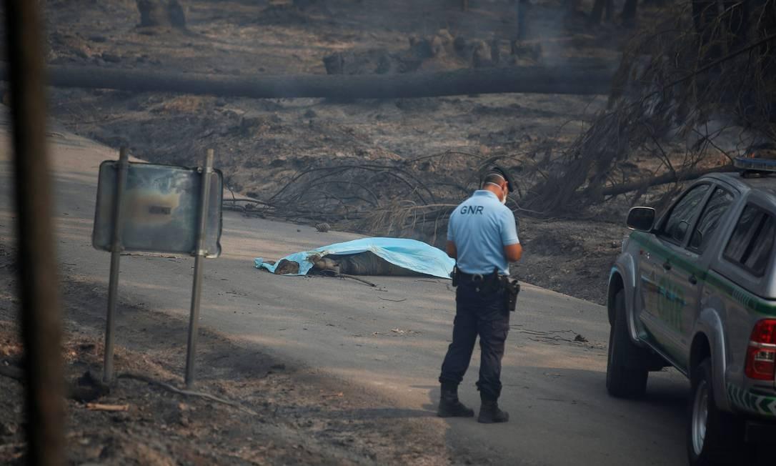 Policial perto do corpo de uma vítima do incêndio em Pedrógão Grande Foto: RAFAEL MARCHANTE / REUTERS