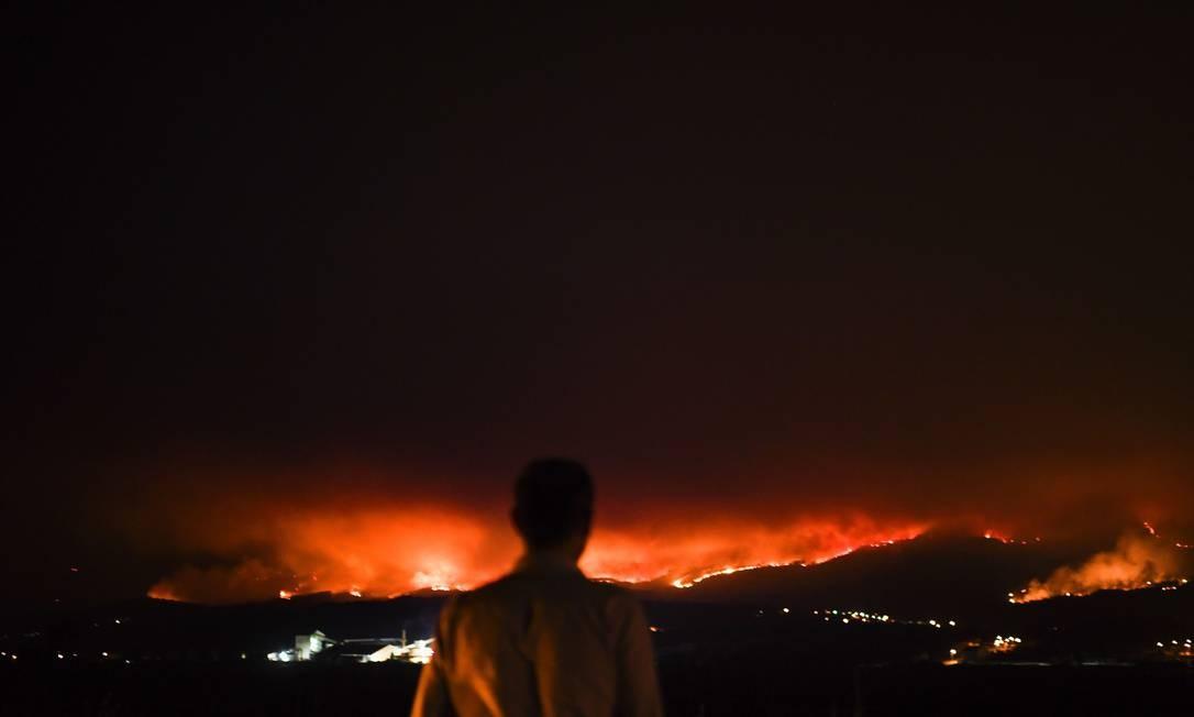 Homem observa as chamas que se alastratam por vários vilarejos no distrito de Leiria Foto: PATRICIA DE MELO MOREIRA / AFP
