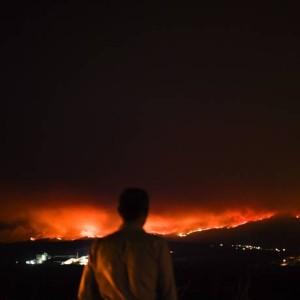 Homem observa as chamas que se alastratam por vários municípios no distrito de Leiria Foto: PATRICIA DE MELO MOREIRA / AFP