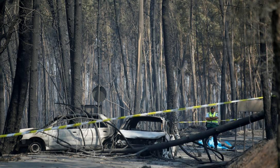 Carros queimados e o corpo de uma das vítimas do incêndio Foto: RAFAEL MARCHANTE / REUTERS
