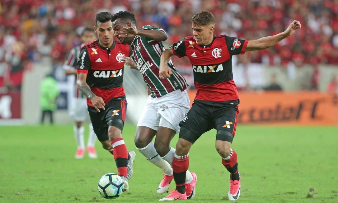 Trauco, autor do segundo gol do Flamengo, observa a disputa de bola entre seu colega de time e Orejuela, do Flu Márcio Alves / Agência O Globo