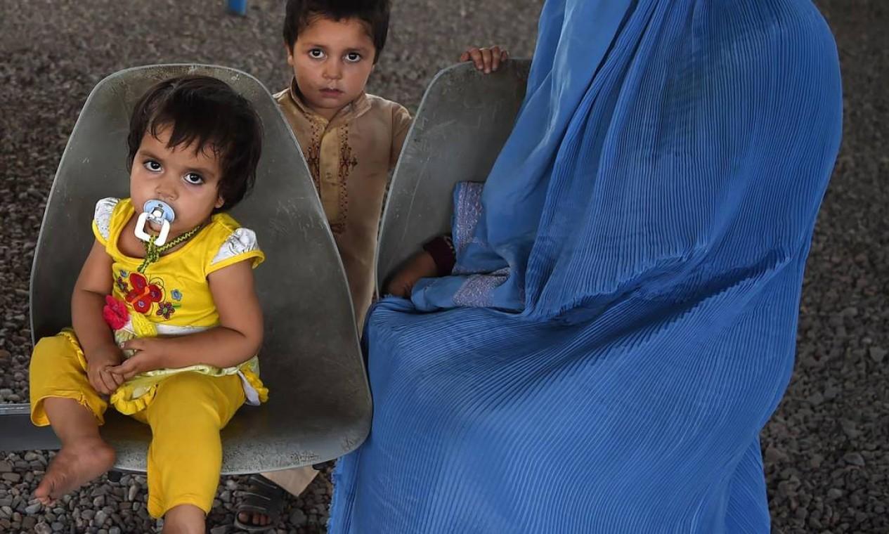 Mulher afegã com os filhos num centro para refugiados no Paquistão Foto: ABDUL MAJEED / AFP