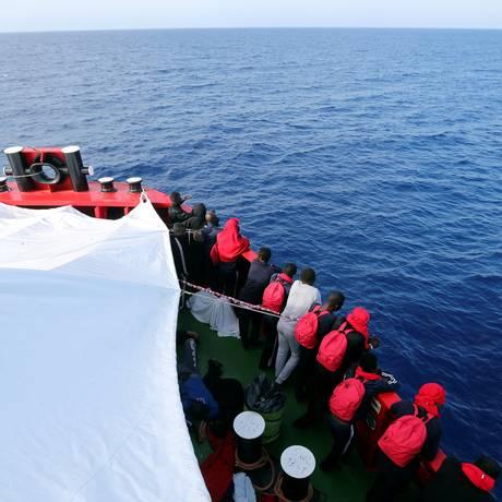 Imigrantes olham para o Mediterrâneo após serem resgatados por barco de uma organização humanitária na costa da Líbia Foto: STEFANO RELLANDINI / REUTERS