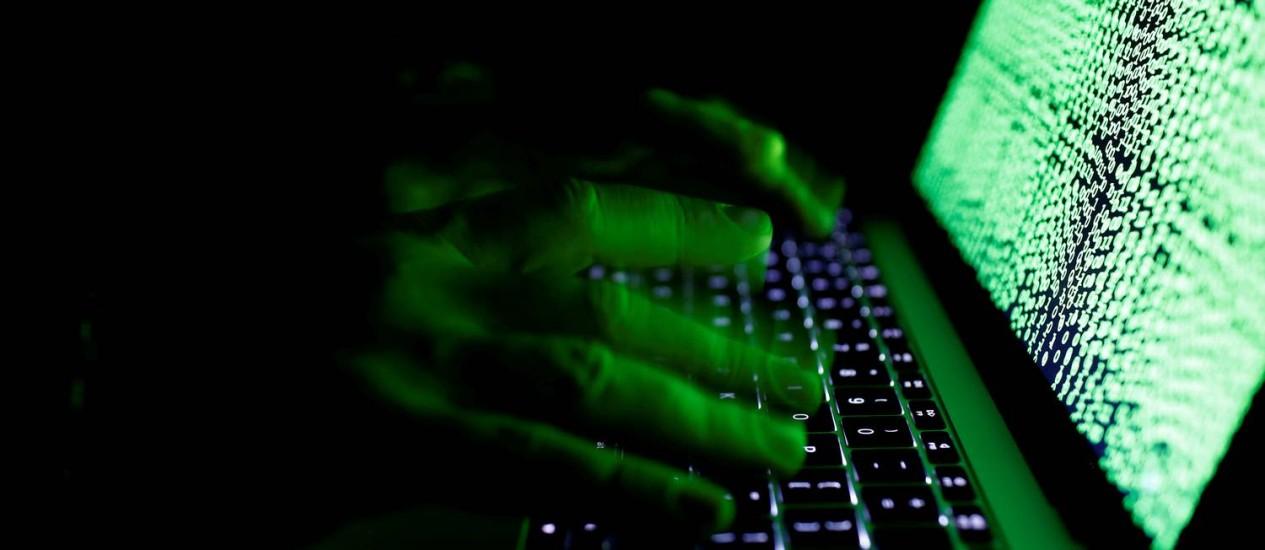 Por trás de computadores, pessoas criam redes de contas falsas para viralizar informações Foto: Kacper Pempel / Reuters