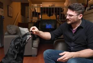 Brett Hartman dá a sua cadela Cayley, uma labradora de seis anos, gotas de canabidiol para liviar ansiedade do animal Foto: AFP/ROBYN BECK