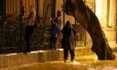 Pessoas seguram em grade para se proteger de alagamento na Rua Jardim Botânico Foto: Marcelo Theobald / Agência O Globo