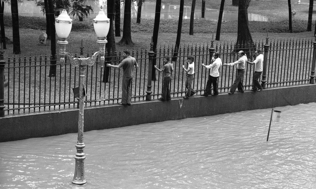 Caminhar agarrado às grades era a alternativa dos pedestres quando chovia na região do Passeio Público, há mais de 40 anos (23/12/1974) Foto: Antonio Nery / Agência O Globo