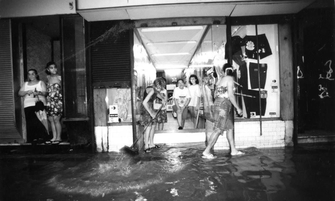 Limpeza de casas e lojas, como a ocorrida na década de 1990 na Tijuca, é uma cena recorrente após alagamentos (01/03/1994) Foto: Hipolito Pereira / Agência O Globo
