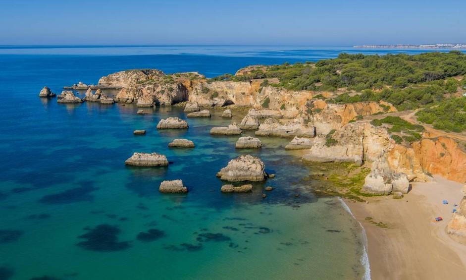 Falésias, rochas e arcos naturais da Praia do Alemão, em Portimão, uma das mais bonitas do Algarve Foto: Associação do Turismo do Algarve / Divulgação