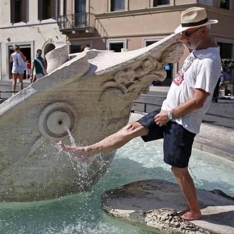 Homem molha o pé na Fontana della Barcaccia, em Roma, uma atitude que neste verão pode render multa de até 240 euros Foto: Max Rossi / Reuters/17-7-2015