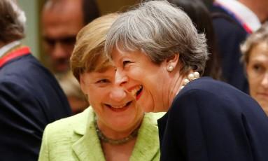 May ri durante encontro com Merkel em cúpula da UE Foto: FRANCOIS LENOIR / REUTERS
