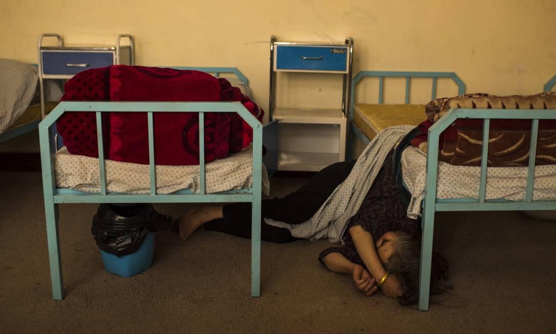 Mulher dorme em chão de centro de reabilitação em Cabul Foto: / Andrew Quilty/The Washington Post
