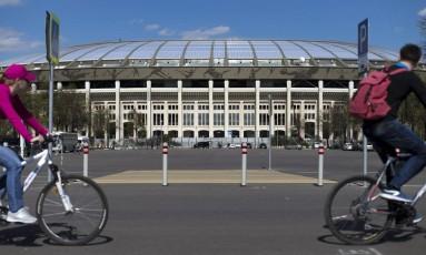 Em obras. Ciclistas passam à frente do estádio Luzhniki, em Moscou: sede dos históricos Jogos Olímpicos de 1980 passa por uma reforma milionária, que gera discussão, como a do Maracanã Foto: Ivan Sekretarev / Ivan Sekretarev/AP