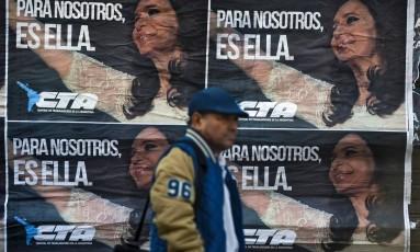 Propaganda maciça. Argentino passa por cartaz pró-Cristina Kirchner em rua de Buenos Aires Foto: EITAN ABRAMOVICH / AFP/14-6-2017